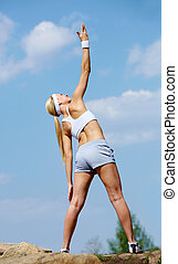 Exercising - Rear view of a young woman in sportswear doing...