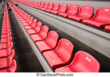 Tribune - Rows of an empty red plastic seats on tribune