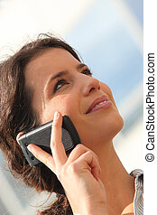 Young woman looking at the sky while using a cellphone