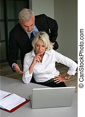 Senior business couple working on a laptop computer