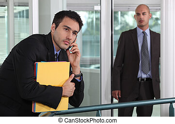 businessman looking at male colleague in workplace