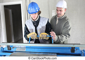 Two men operating machine than cuts sheet metal