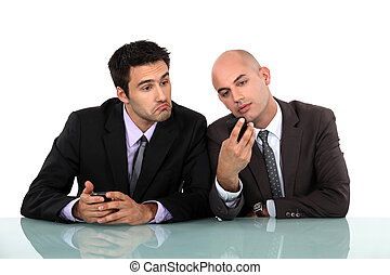 Perplexed man looking at his colleague's mobile phone