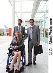 Woman in wheelchair with colleagues outside office building