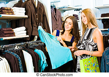 Shopping - Photo of two girls in the clothing store holding...