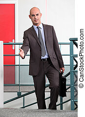 Businessman with briefcase holding out hand