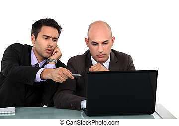 Executives discussing content on a laptop