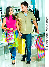 Shopping together - Photo of a young modern couple going...