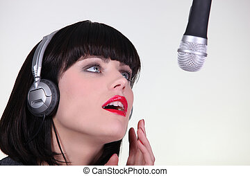 beautiful female singer singing in a studio