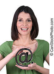 Smiling woman holding the arobase sign