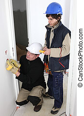 senior electrician and apprentice at work