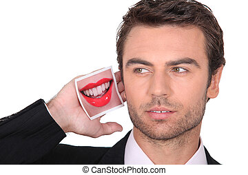 a business man with a mouth picture near his ear