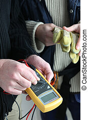 Two electricians with voltmeter
