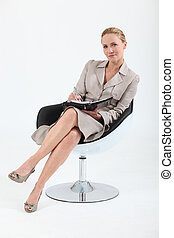 Businesswoman sitting in a swivel chair with a personal...