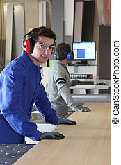 Two factory workers using band-saw