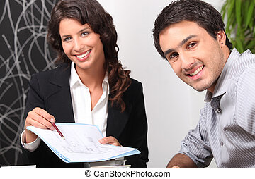Saleswoman showing client where to sign