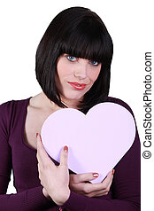 a brunette woman with a heart shaped box