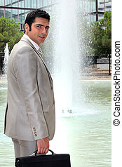 Businessman standing in front of a fountain
