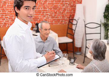 Young waiter approaching an older couple to take their order in a restaurant