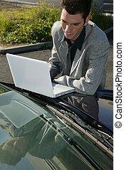Businessman resting a laptop on his car bonnet