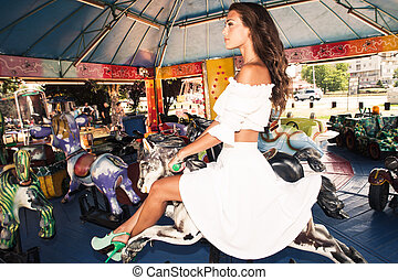 merry go round - beautiful young woman in white dress...