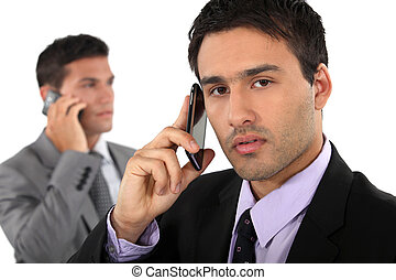 Two businessmen on their mobile telephones
