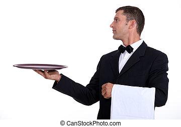 A waiter holding an empty tray