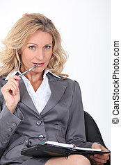 Blond woman chewing pen