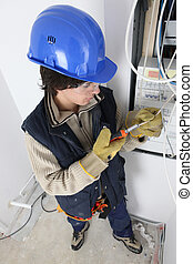 Young man repairing a distribution board