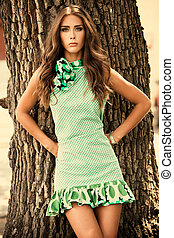 elegant in wood - elegant young woman in green dress stand...