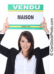 Real estate agent with sold house sign