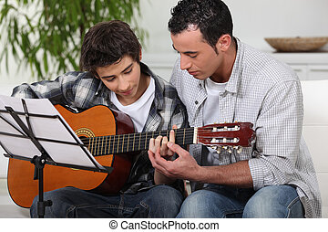 Father teaching son the guitar