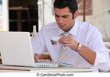 Man using a laptop computer in a cafe