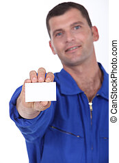 Man in blue overalls holding a business card left blank for...
