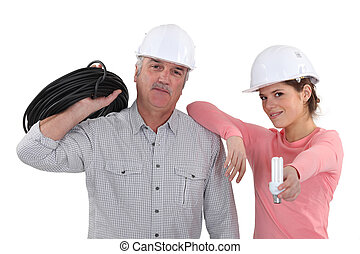 experienced electrician and young female apprentice