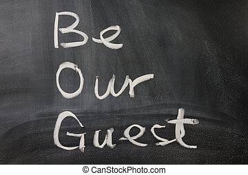 Be our guest words written  on the blackboard