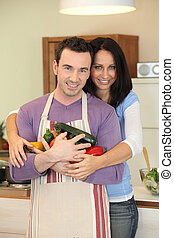 Couple holding a variety of vegetables