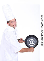 Chef with an sign on his frying pan