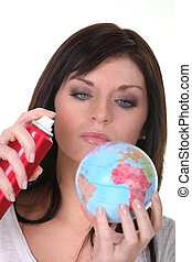 Woman spraying miniature globe