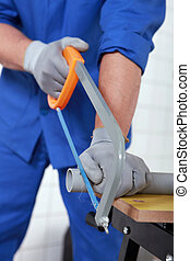 Plumber sawing grey plastic pipe