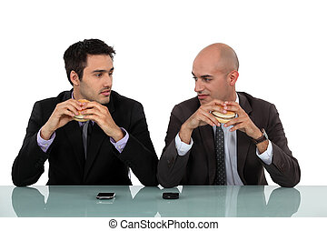Two businessmen sat eating hamburgers