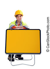 little child dressed in road man is leaning against a yellow...