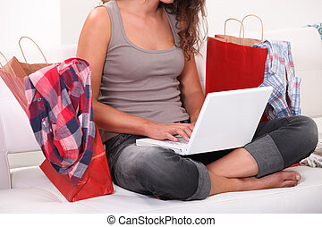 Woman sitting on sofa with computer and bags