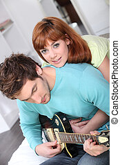 Woman embracing boy playing guitar