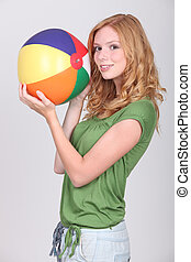 Female teenager holding inflatable beach ball
