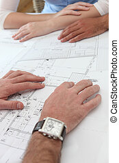Close-up of architects examining floor-plans