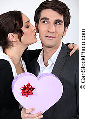 Woman kissing man with gift