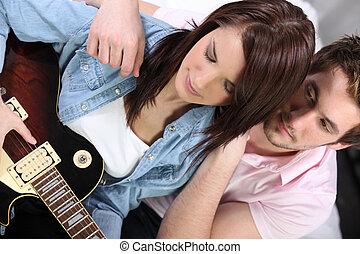 Man looking girl playing guitar