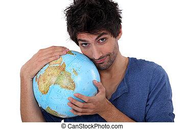 Handsome man hugging a globe