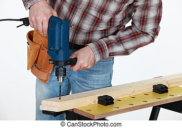 Carpenter drilling into wooden plank